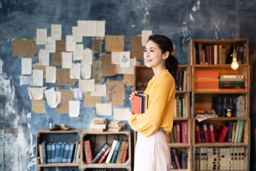 英語の勉強本を持つ女性